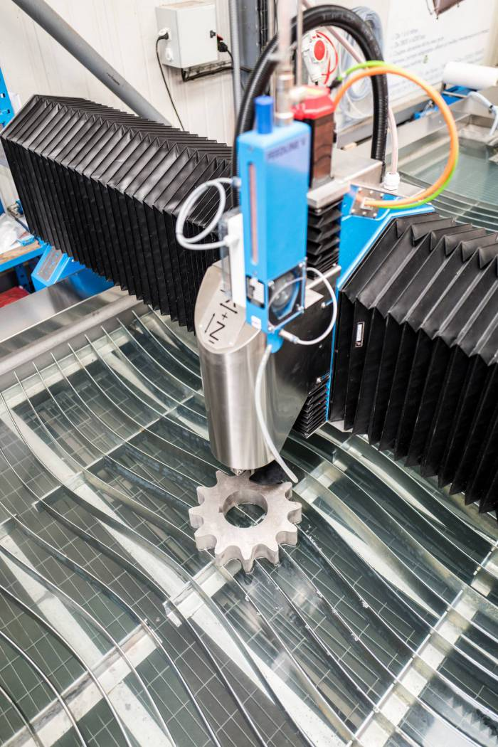 Machine de découpe jet d'eau en tran de découper une pièce en acier dans l'atelier de production LDSA